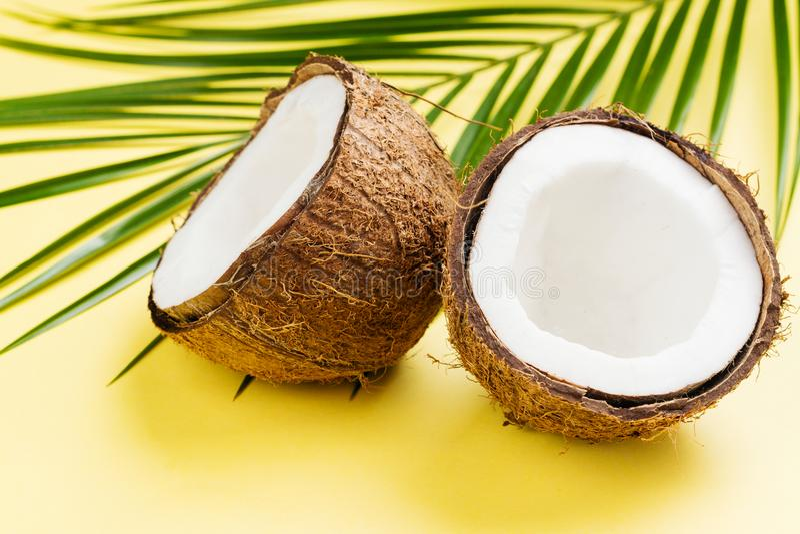 Moitiés et feuilles de noix de coco sur le fond jaune image libre de droits