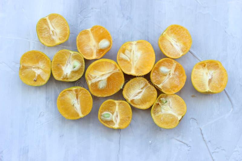Moiti?s lumineuses d'agrume et jus d'orange sur le fond gris La vue ? partir du dessus image libre de droits