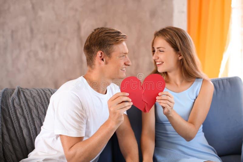 Moitiés se reliantes de jeunes couples du coeur brisé sur le sofa à la maison images libres de droits