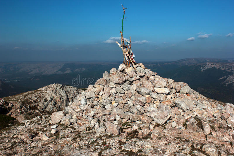 Mojón de piedra con pegar polos Pila de rocas en el top de la montaña fotografía de archivo libre de regalías