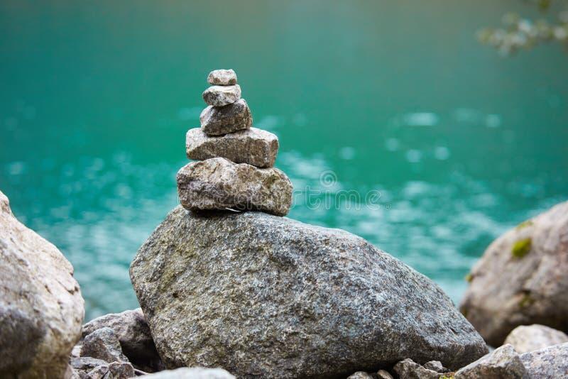 Mojón en la orilla de un lago de la montaña imagen de archivo