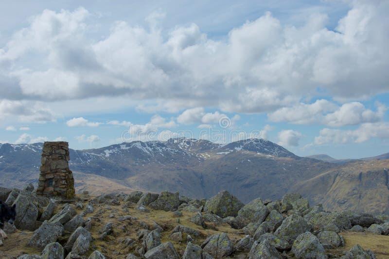 Mojón y rocas en la cumbre de la montaña del distrito del lago; riscos nevados en distancia fotografía de archivo
