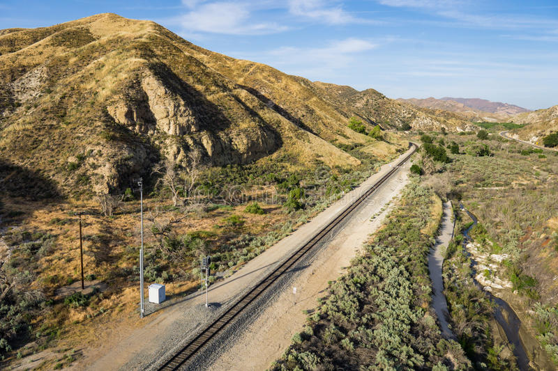 Mojave Desert Railroad Track. Straight line of railroad tracks lead through a valley in the Mojave Desert of California royalty free stock image