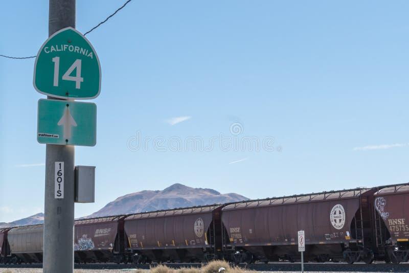 MOJAVE KALIFORNIEN: Tecken för Kalifornien stathuvudväg 14, med drevet i bakgrund fotografering för bildbyråer