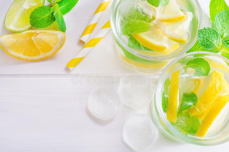 Mojito напитка лета с известкой, лимоном и мятой, с кубами льда на белой деревянной предпосылке r стоковое фото