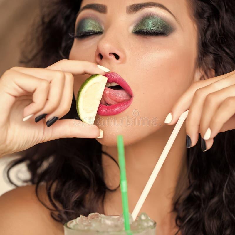 Mojito bevente della giovane donna che lecca calce fotografia stock libera da diritti
