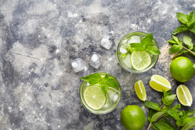 Mojito cocktail alcohol bar summer refreshment drink traditional Cuba beverage top view copy space two highball glass. With rum, citrus slice, mint, lime, soda stock images