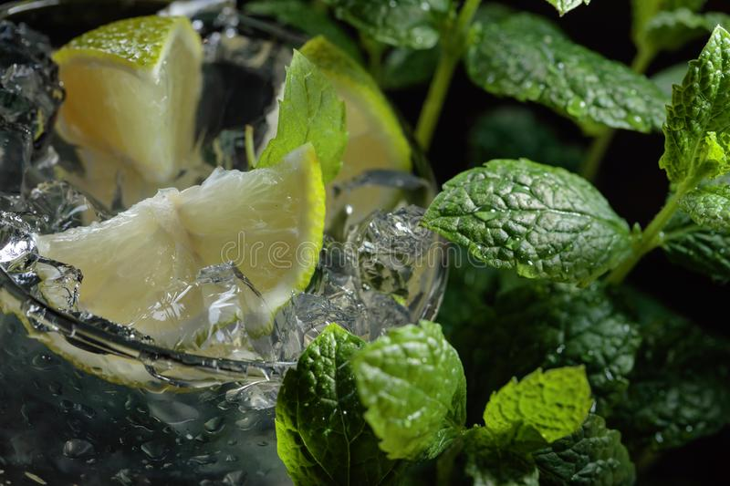 Mojito cocktail drink with lime, ice and mint. On dark background. Selective focus royalty free stock photos