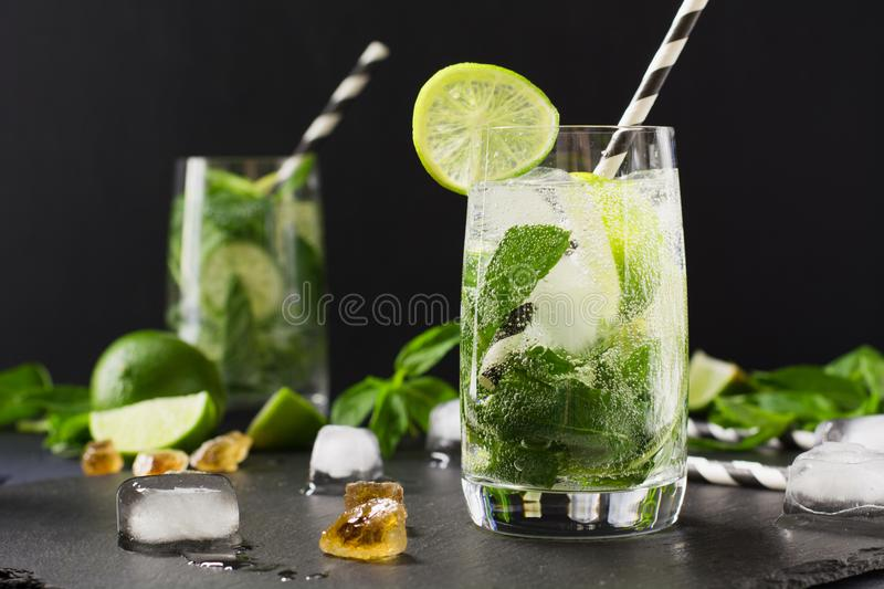 Mojito cocktail in glass on black table. Low key photo. Close up. Mojito cocktail in glass with garnish on black table. Low key photo. Close up stock images