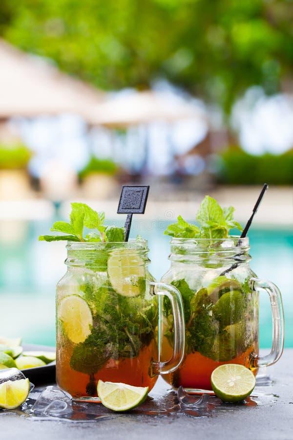Mojito cocktail i glasburkar på blå vattenbakgrund Kopiera utrymme fotografering för bildbyråer