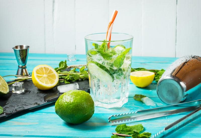Mojito cocktail with lime and mint in highball glass on a blue wood table. Drink making tools and ingredients for cocktail.  royalty free stock photography