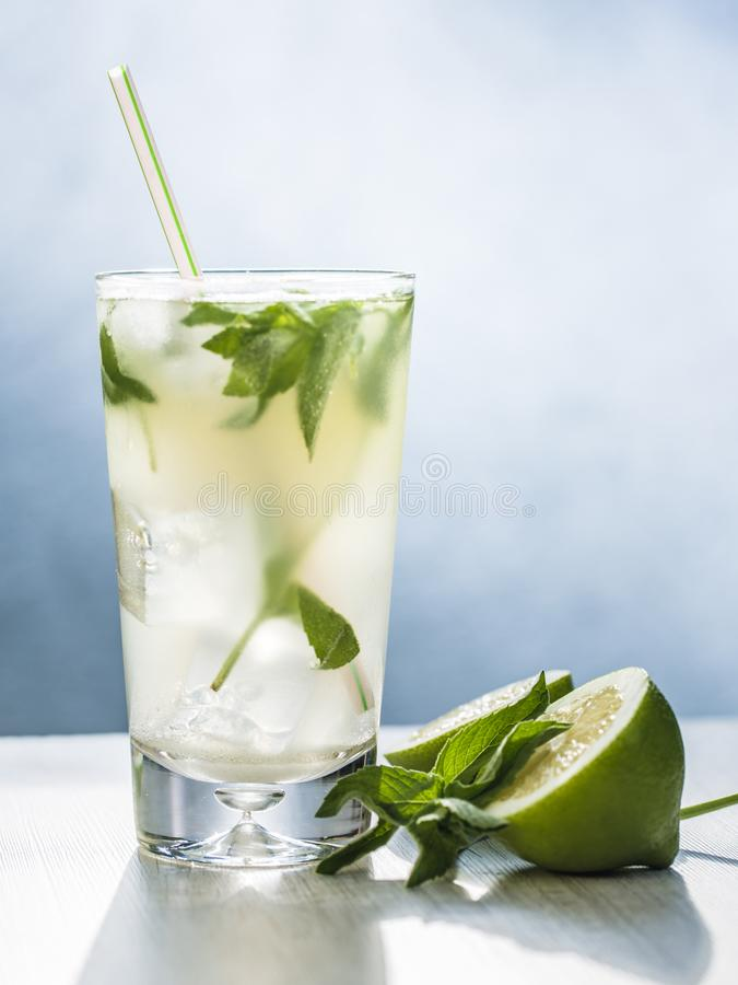 Mojito cocktail with lime, sugar, ice and mint leaves in the gray background. stock photo