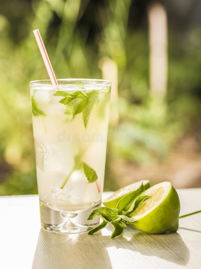 Mojito cocktail with lime, sugar, ice and mint leaves in the sunlight. stock photography