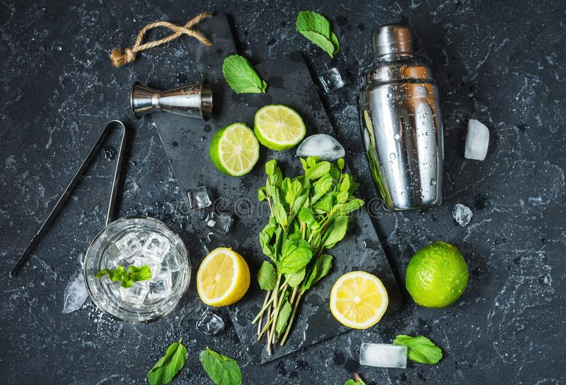 Mojito cocktail making. Mint, lime, glass, ice, ingredients and shaker on black stone background. Top view royalty free stock photography