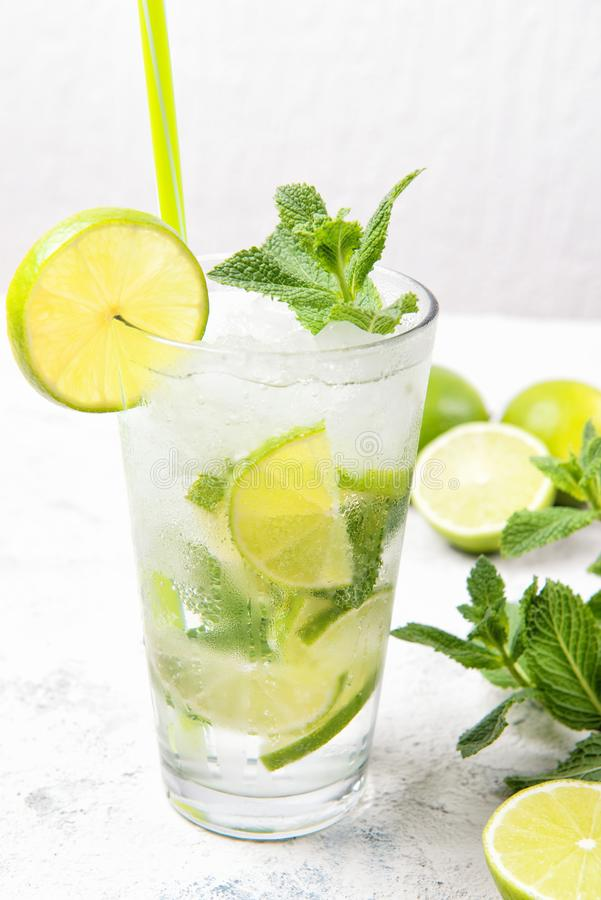 Mojito cocktail with fresh limes and mint leaves in a glass on a light grey stone background royalty free stock image