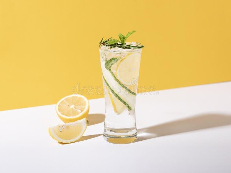 Mojito coctail med citronen och mintkaramellen i exponeringsglas p? gul bakgrund f?r citrus vatten f?r sommar drinkis f?r karaff  arkivfoton