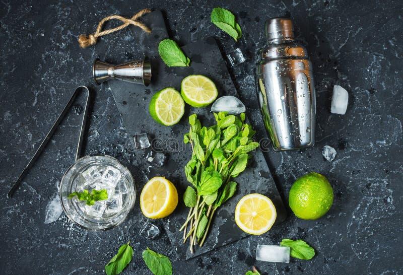 Mojito coctaildanande Mintkaramell, limefrukt, exponeringsglas, is, ingredienser och shaker på svart stenbakgrund Top beskådar royaltyfri fotografi