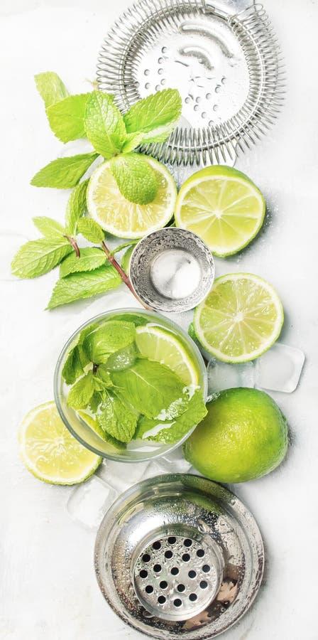 Mojito coctailingredienser, coctail i exponeringsglas och stånghjälpmedel, drinkbakgrund, bästa sikt, vertikalt baner royaltyfria foton