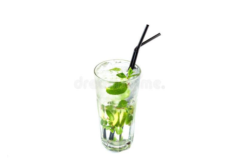 Mojito con calce e la menta in una tazza di vetro con una paglia su un fondo bianco isolato immagine stock