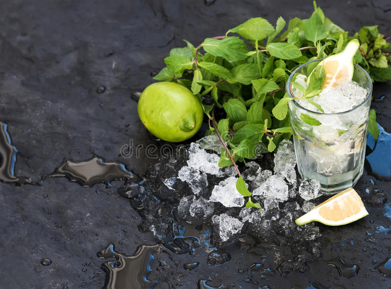 Mojito cooking set. Bunch of fresh mint, lime, chipped ice and coctail glass over black slate stone backdrop, copy space. Mojito cooking set. Bunch of fresh mint stock photo