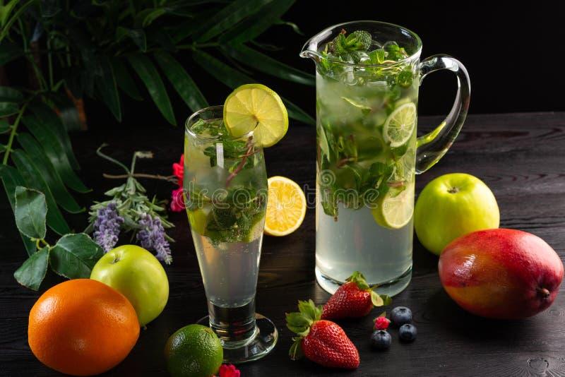 Mojito lemonad i en tillbringare och ett exponeringsglas och frukter på en mörk träbakgrund royaltyfria bilder
