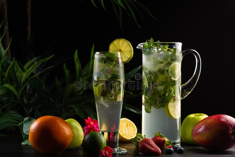 Mojito lemonad i en tillbringare och ett exponeringsglas och frukter arkivfoto