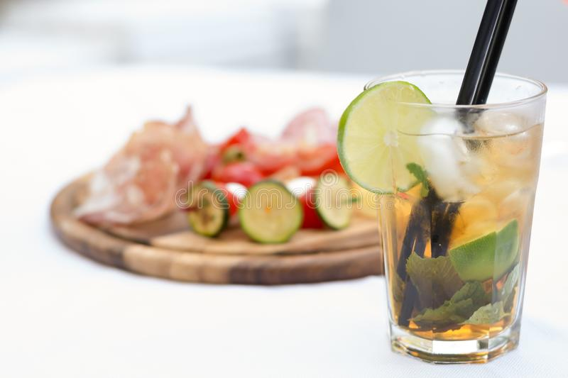 Mojito with snacks as aperitif. Aperitif in a bar with cocktail and snacks royalty free stock photo