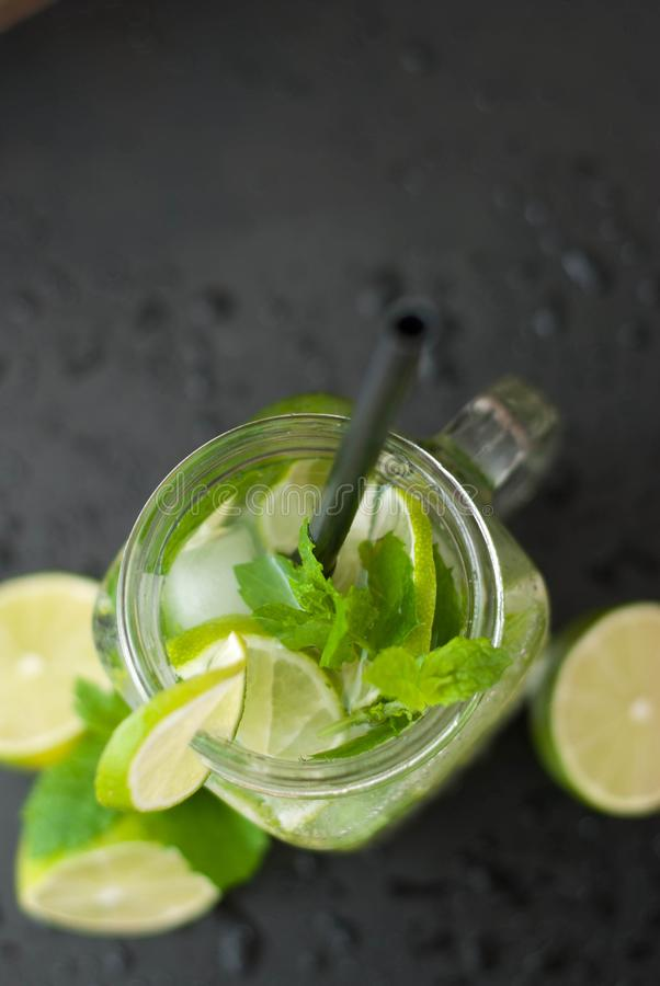 Mojito Summer Cocktail on Black background Water Drops Lime Citrus Fruit Mint Leaves royalty free stock image