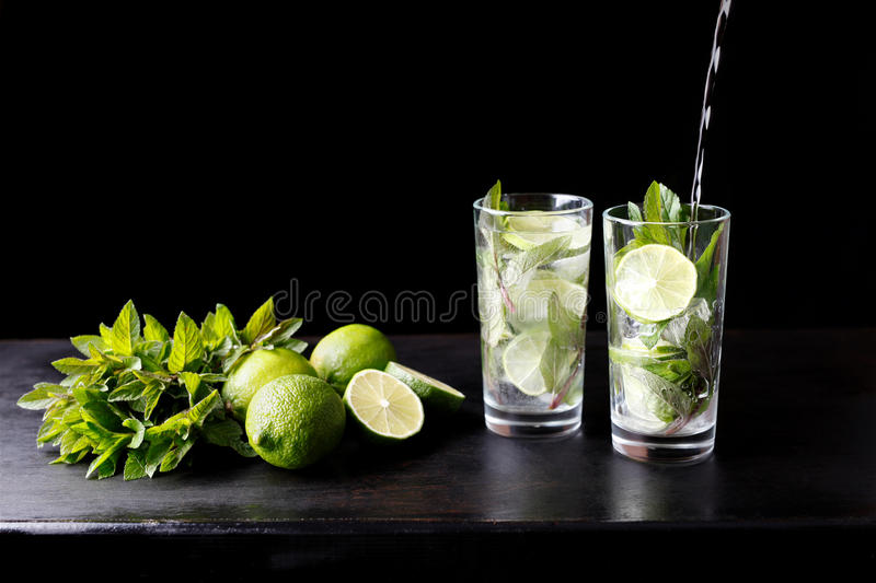 Mojito traditional beach refreshing cocktail alcohol drink in glass bar preparation pouring soda water, lime, mint royalty free stock images