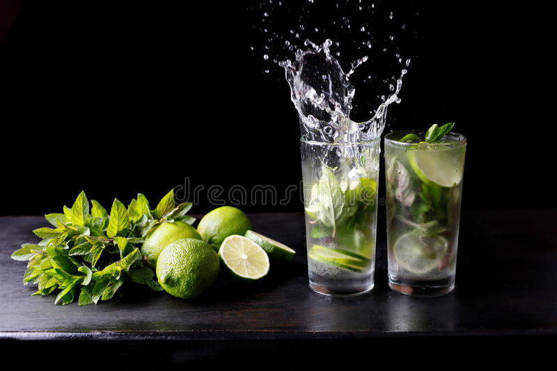 Mojito traditional beach refreshing cocktail alcohol drink in glass with splash, bar preparation soda water, lime, mint royalty free stock photo