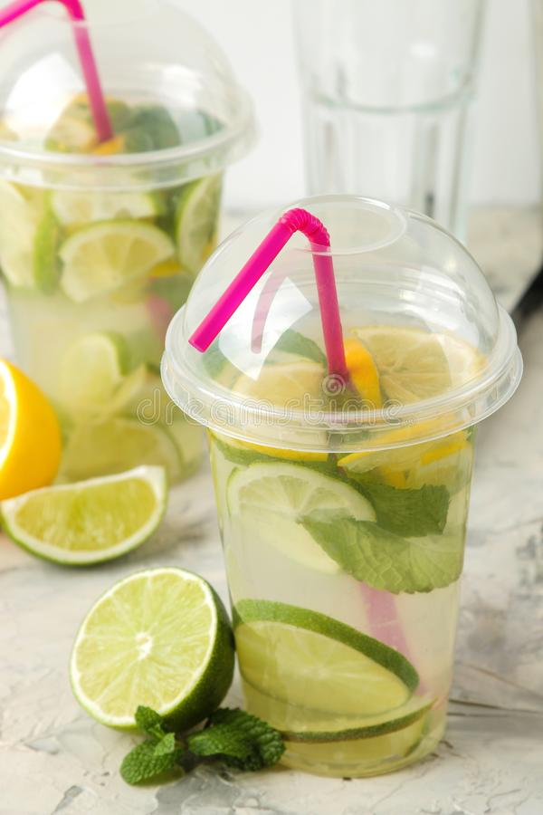 Mojitococktail in een plastic glas met kalk, munt en citroen op een lichte concrete lijst maak een mojito stock fotografie
