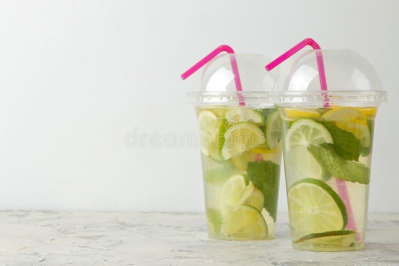 Mojitococktail in een plastic glas met kalk, munt en citroen op een lichte concrete lijst maak een mojito royalty-vrije stock fotografie