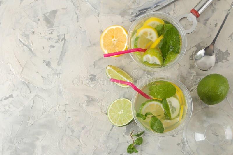 Mojitococktail in een plastic glas met kalk, munt en citroen op een lichte concrete lijst maak een mojito Hoogste mening royalty-vrije stock foto's