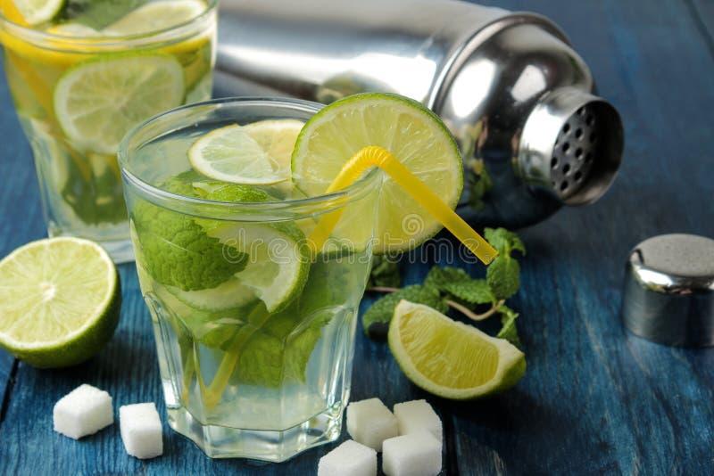 Mojitococktail in glas/glas- met kalk, munt en citroen en bartoebehoren op een blauwe houten lijst maak een mojito stock foto's