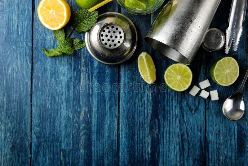 Mojitococktail in glas/glas- met kalk, munt en citroen en bartoebehoren op een blauwe houten lijst maak een mojito Hoogste mening royalty-vrije stock foto's