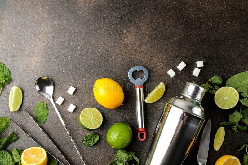 Mojitococktail in glas/glas- met kalk, munt en citroen en bartoebehoren op een donkere concrete achtergrond het koken mojito bove stock afbeeldingen