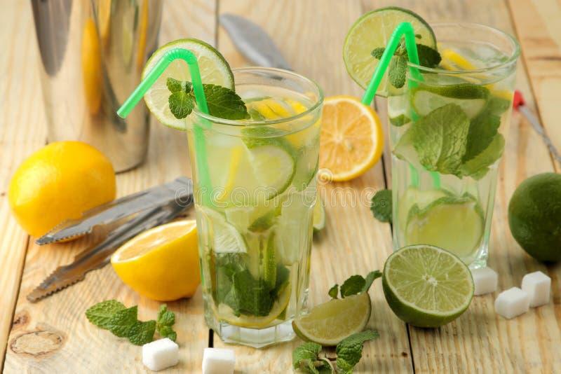 Mojitococktail in glas/glas- met kalk, munt en citroen en bartoebehoren op een natuurlijke houten lijst maak een mojito stock foto's