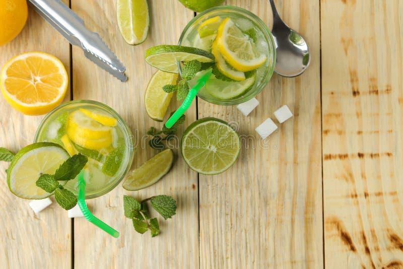 Mojitococktail in glas/glas- met kalk, munt en citroen en bartoebehoren op een natuurlijke houten lijst maak een mojito Hoogste m stock afbeelding