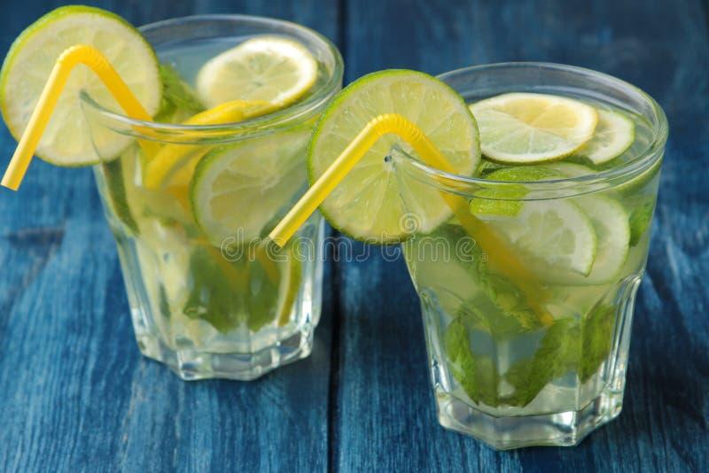 Mojitococktail in glas/glas- met kalk, munt en citroen op een blauwe houten lijst maak een mojito royalty-vrije stock foto