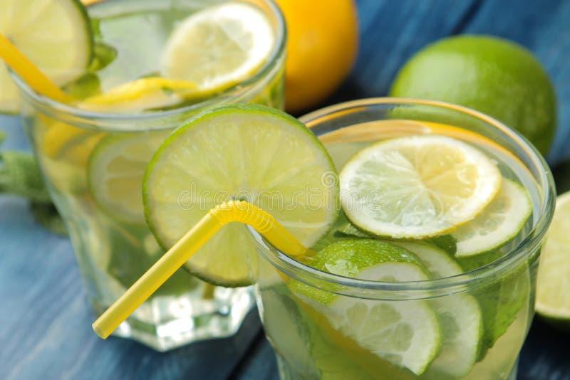 Mojitococktail in glas/glas- met kalk, munt en citroen op een blauwe houten lijst maak een mojito stock afbeeldingen