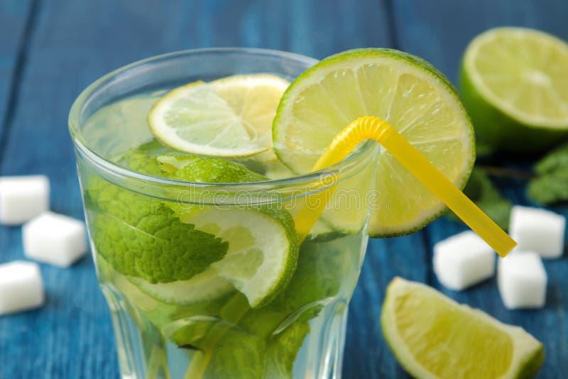 Mojitococktail in glas/glas- met kalk, munt en citroen op een blauwe houten lijst maak een mojito stock foto
