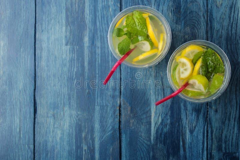 Mojitococktail in glas/glas- met kalk, munt en citroen op een blauwe houten lijst maak een mojito Hoogste mening royalty-vrije stock afbeelding