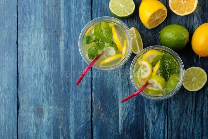 Mojitococktail in glas/glas- met kalk, munt en citroen op een blauwe houten lijst maak een mojito Hoogste mening royalty-vrije stock fotografie