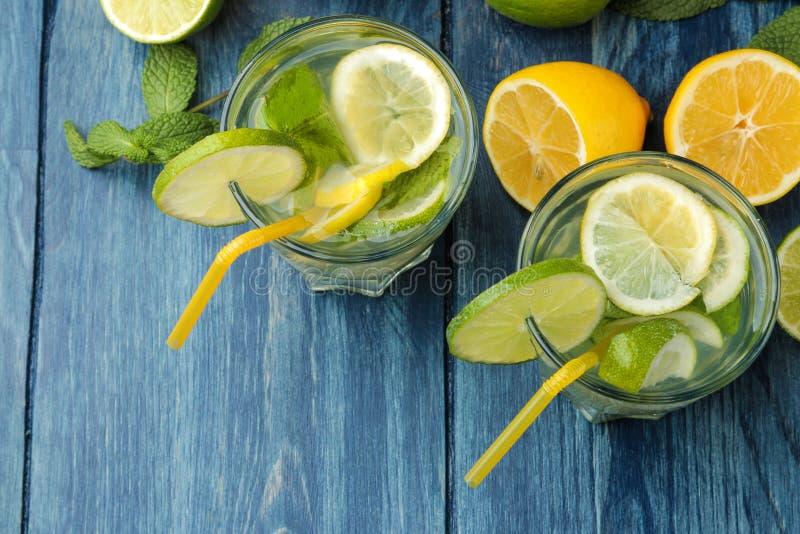 Mojitococktail in glas/glas- met kalk, munt en citroen op een blauwe houten lijst maak een mojito Hoogste mening stock foto