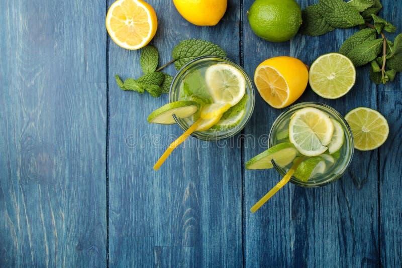 Mojitococktail in glas/glas- met kalk, munt en citroen op een blauwe houten lijst maak een mojito Hoogste mening stock fotografie