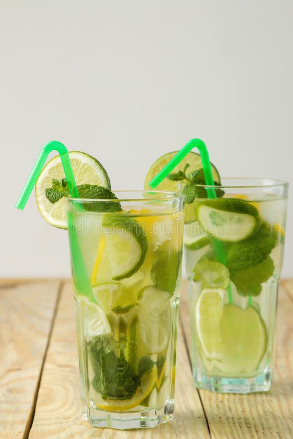 Mojitococktail in glas/glas- met kalk, munt en citroen en op een natuurlijke houten lijst maak een mojito stock fotografie