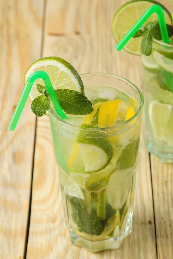 Mojitococktail in glas/glas- met kalk, munt en citroen en op een natuurlijke houten lijst maak een mojito stock foto's