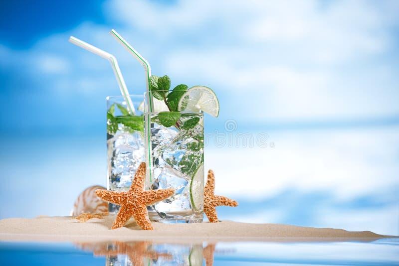 Mojitococktail op strandzand en tropisch zeegezicht stock afbeeldingen