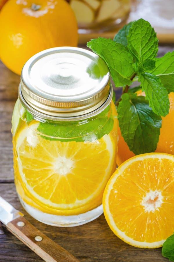 Mok heerlijke verfrissende drank van oranje fruit met munt stock fotografie