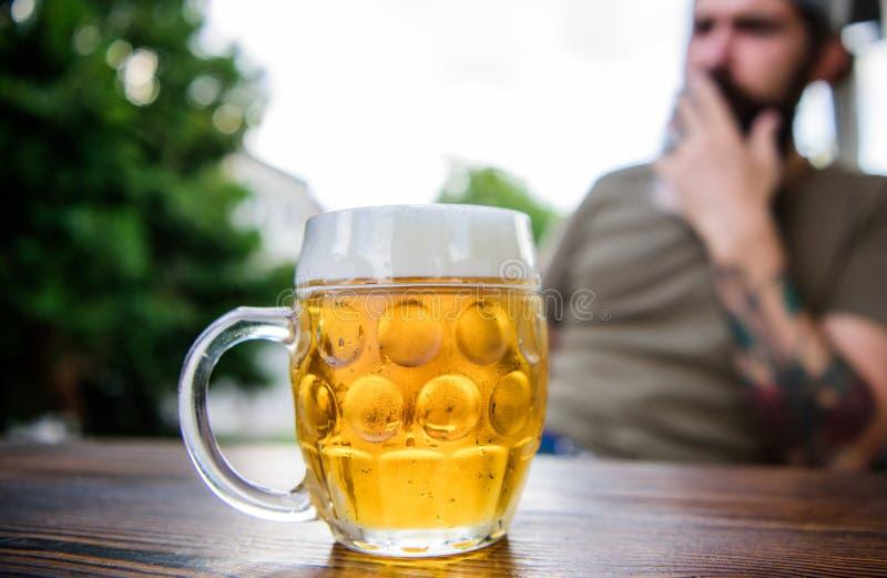 Mok koud vers bier op lijst dichte omhooggaand De mens zit koffieterras genietend van bier defocused Alcohol en barconcept creati royalty-vrije stock foto's